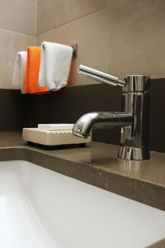 bathroom concrete counter top with undermount sink and faucet